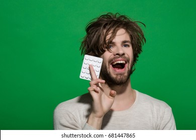 Treatment and hypnotic tablet. Guy hold dieting pill and vitamin. Man with pills in blister pack. Drug and antidepressant. Health and medicine.