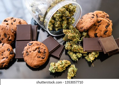 Treatment of medical marijuana for use in food, black background. Chocolate and Cookies with cannabis and buds of marijuana on the table. Concept of Cookies and chocolate with cannabis herb CBD.