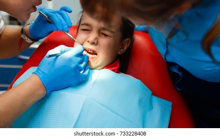 Treatment in the office of a children s dentist to put seal in the teeth of a small girl