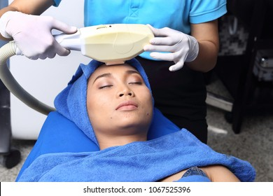 Treatment on Asian Woman as patient to make skin smooth bright and cure acne with medical beauty device instrument cold process on face in hospital clinic with acne wart