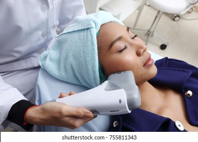 Treatment on Asian Woman as patient to make skin smooth bright and cure acne with medical beauty device instrument cold process on face in hospital clinic