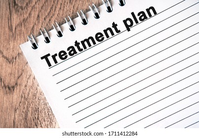 Treatment plan - black text on a white notebook with lines on a wooden table