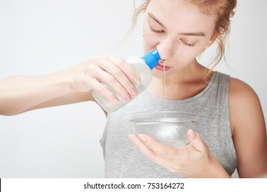 Treatment and prevention of the common cold. The girl washes out the nose with saline