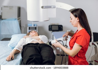 Treatment of urethral stones by non-invasive extracorporeal shock wave lithotripsy. Professional woman doctor working with modern lithotripter to break up stones for her female patient