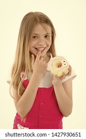 Treats for holidays. Kid rewarded for good behavior with sugary treats. Girl cute smiling face holds sweet donut. Girl likes sweets as donuts. How tame childs sweet tooth. Treats and dieting concept.