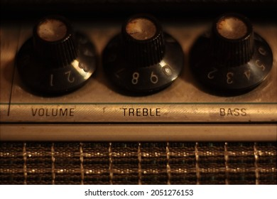 Treble, volume and bass control knobs on 1960s vintage guitar amp head. Warm color temperature, shallow depth of field, macro.