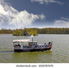 TREBON, CZECH REPUBLIC - APRIL 29, 2012: Sightseeing tour boat at the Svet Pond (Pond World) near Trebon. Trebon is a old historical town in South Bohemian Region