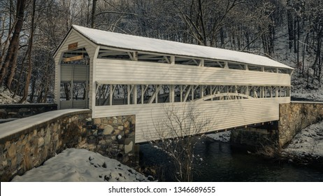 TREDYFFRIN TOWNSHIP, PENNSYLVANIA – MAR 4, 2019: Snow-covered historic Knox Bridge spans over Valley Creek in Valley Forge National Historic Park in Chester County.