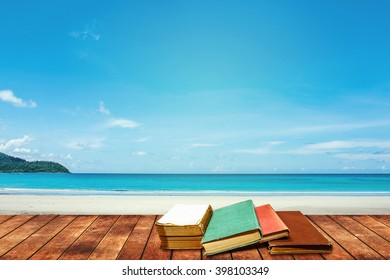 tree aged book and grunge paper on wooden platform beside tropical beach and blue sea on day noon light.