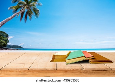 tree aged book and grunge paper on wooden platform beside tropical beach and blue sea on day noon light back to school concept.