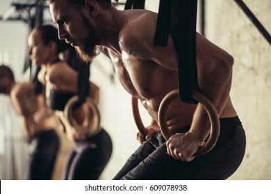 tree attractive young male and female adults doing pull ups on bar in cross fit training gym with brick walls and black mats