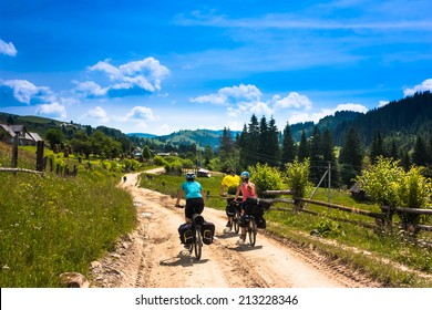Tree bicyclist in sunny mountain landscape. Green grass, trees and blue sky