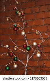 Tree branch painted and decorated for Christmas against a brick wall.