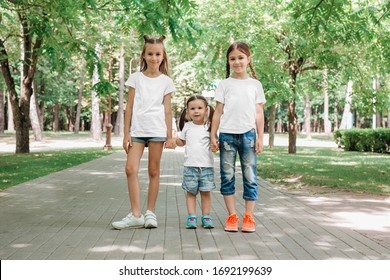 Tree children in white t-shirts stand holding hands in park. Mock up.