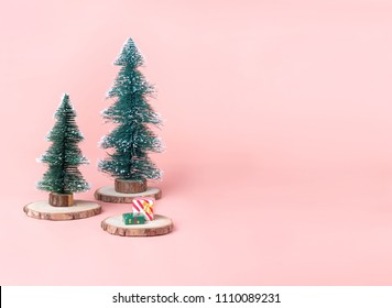 Tree Christmas tree on wood log slice with present box on pastel pink studio background.Holiday festive celebration greeting card with copy space for display of design or content