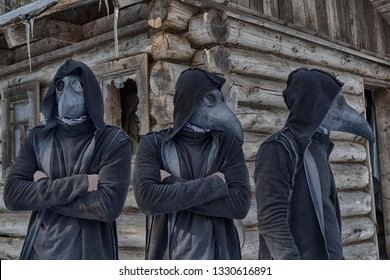Tree copies (clones) of a man in a mask of a plague doctor and a hood in the forest against the background of an abandoned hut, look in different directions. Something mystical and fabulous.