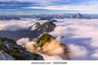 Tree covered mountain tops peeking over soft clouds with distant mountains in the background taken from the top of the Golden Ears Mountain Summit