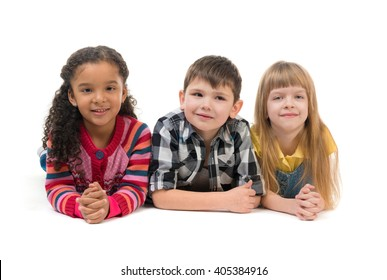 tree cute children lying on the floor in a studio isolated on white background