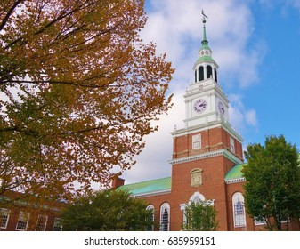 With a tree in fall colors filling most of the left half of the frame this is a nice view of the  library bell tower and blue sky on the campus of Dartmouth College in Hanover, New Hampshire.
