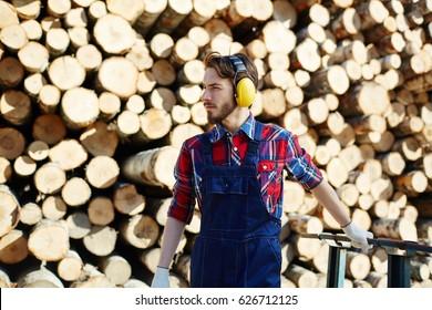 Tree felling worker with headphones pulling cart