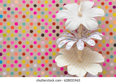 Tree flowers made of paper with different patterns hanging in from of a background made of multi colored dots