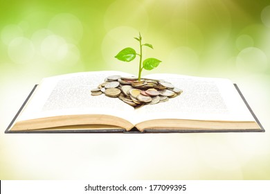 """tree growing from book with coins / A big open book with coins and tree. """"Reading makes you richer"""" concept."""