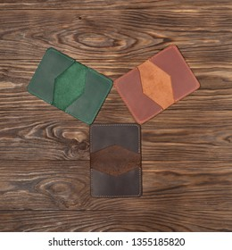 Tree handmade different colour leather cardholders on wooden background. Stock flat lay photo. Green, ginger and brown cardholders on photo.
