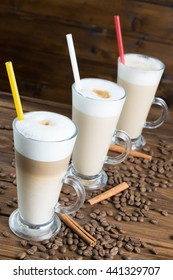 Tree latte with coffee seeds and cinnamon sticks on wooden background