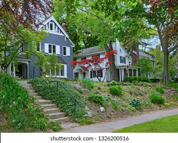 tree lined neighborhood of middle class suburban houses with gables and siding