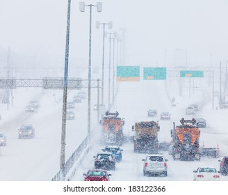 Tree Lined-up Snowplows Removing the Snow the Highway on a Cold Snowy Winter Day