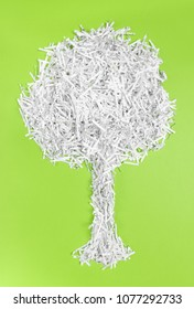 Tree made of shredded paper, on bright green background. Recycling and environment protection concept.