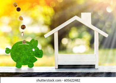A tree piggy bank and a home wooden put on the table in the public park, saving growing money for buy a new house or real estate owner in the future and richness concept.