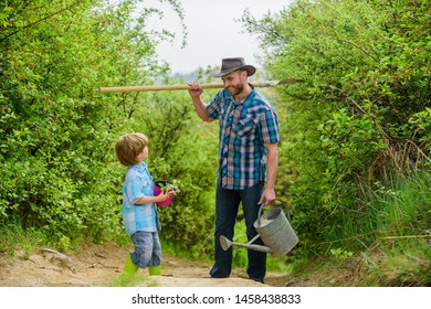 Tree planting tradition. Little helper in garden. Planting flowers. Growing plants. Boy and father in nature with watering can and shovel. Dad teaching son care plants. Arbor day. Planting trees.