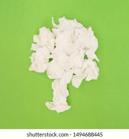 Tree pollen allergies minimal concept with paper tissues shaped in tree on green background, flat lay, top view