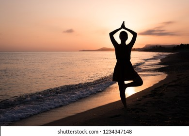 Tree Pose Vriksasana Yoga by young woman at sunrise on a beach by young female. Meditating female.