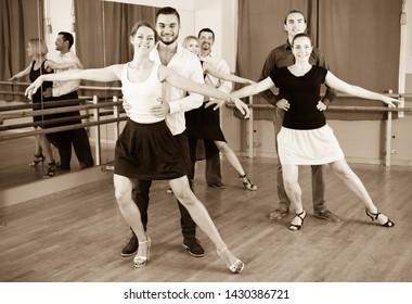 Tree positive  elegant couples dancing waltz in dancing-class