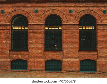 Tree rounded vintage windows on the factory red brick wall.