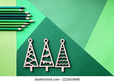 Tree simple wooden trees and many various shade of green color pencils lay on the green color gradation paper background, original craft and diy concept for kid and kindergarten