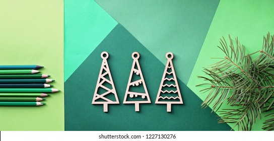 Tree simple wooden trees and many various shade of green color pencils lay on the green color gradation paper background, branches of different fir trees, original craft and diy for kid, banner