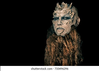 Tree spirit and fantasy concept. Monster with sharp thorns and warts. Druid behind old bark isolated on black. Goblin with horns on head. Man with dragon skin and bearded face, copy space