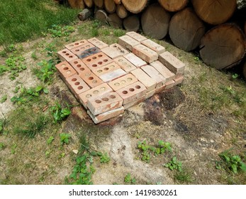 tree stump with red bricks and stacked firewood