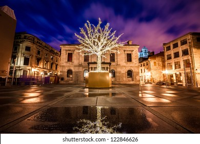 Tree surrounded by decorative lights for Christmas among buildings of Old Montreal and part of the reflection of the tree in the water in the foreground at night