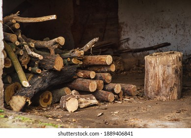 Tree trunks harvested for the winter in the form of decks. Garage with wood decks. Shelter for wood fuel