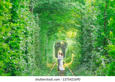 a tree tunnel and a railroad track. the couple in love stand face to face