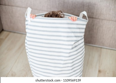 Tree years old girl playing home hide and seek, using fabric basket. A child hides in the basket