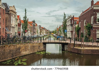 Tree-lined long canal with small bridge, brick houses on its bank and cloudy day at Gouda. Very popular day trip destination, is famous for its tasty Gouda cheese. Southern Netherlands.