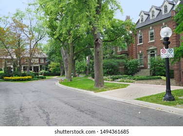 Tree-lined residential street with large brick detached houses