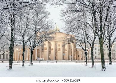 Trees of Berlin Tiergarten and illuminated Brandenburg gate (Brandenburger Tor) in snow, Berlin, Germany, Europe, Retro filtered style