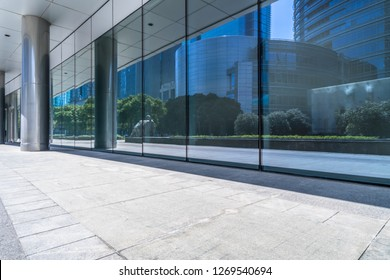 trees and buildings reflected on clean glass wall,china.