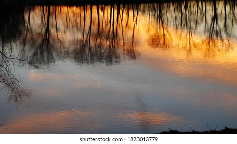 Trees and clouds reflected on the Delaware River at sunset, orange blue purple sky